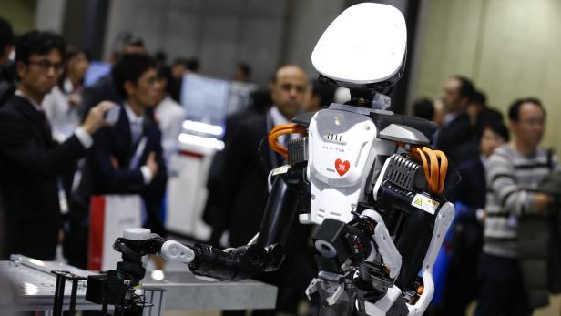 Visitors look at a Kawada Nextage robot at the Int