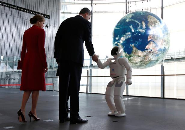 Spain's King Felipe shakes hands with Honda Motor's humanoid robot Asimo at Miraikan in Tokyo
