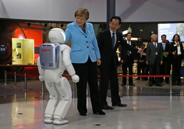 """Angela Merkel touches bi-ped humanoid robot """"Asimo"""" at the National Museum of Emerging Science and Innovation in Tokyo"""