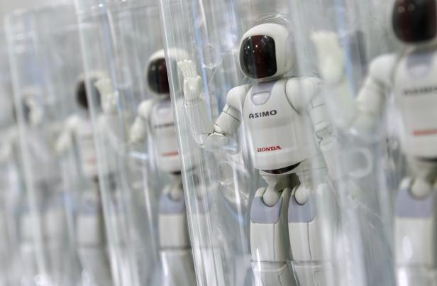 The logos of the Honda Motor Co are seen on the company's ASIMO dolls displayed at the company showroom in Tokyo