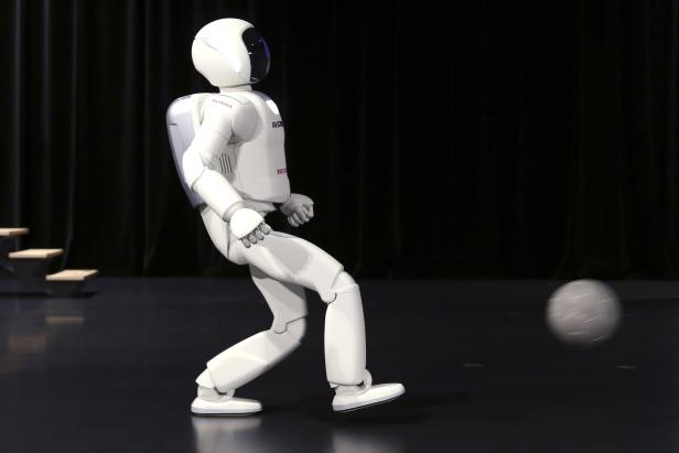 Honda's latest version of the Asimo humanoid robot kicks a soccer bowl during a presentation in Zaventem near Brussels
