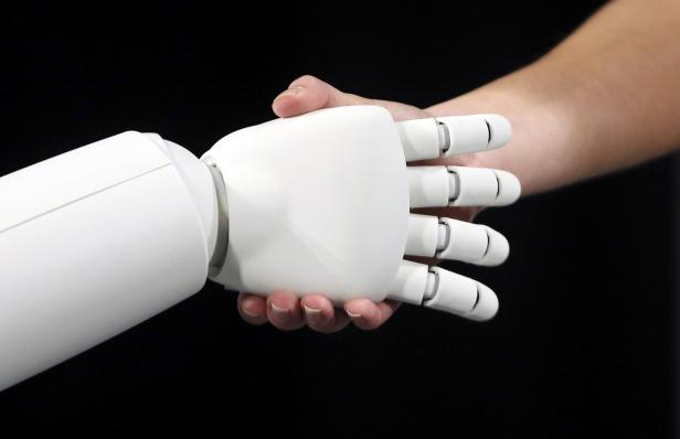 Honda's latest version of the Asimo humanoid robot shakes hands during a presentation in Zaventem near Brussels