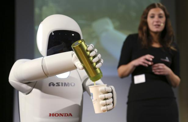Honda's latest version of the Asimo humanoid robot pours a drink into a cup during a presentation in Zaventem near Brussels