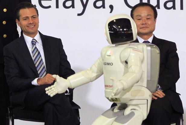 Honda Motor Co's President and CEO Ito sits next to Mexican President Pena Nieto as they watch Honda's ASIMO robot entertain the crowd during the opening of Honda's new automobile plant in a suburb of Celaya, Guanajuato
