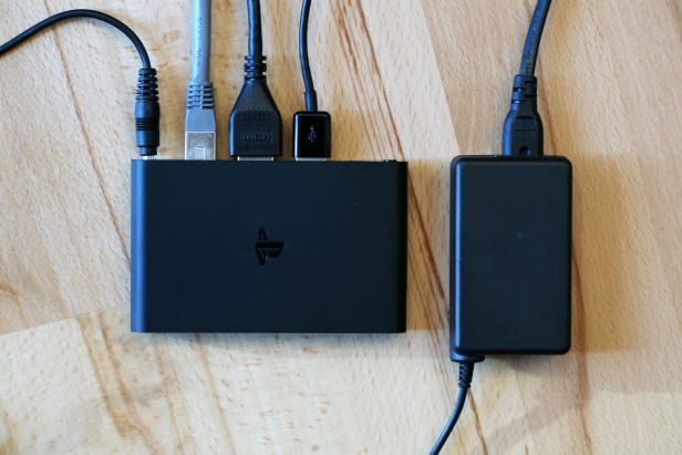 PS TV mit Kabeln an allen Anschlüssen und Netzteil