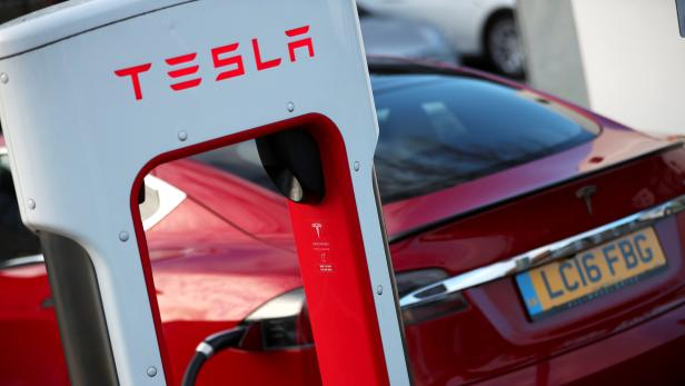 A Tesla car is charged at a Tesla dealership in West Drayton, just outside London