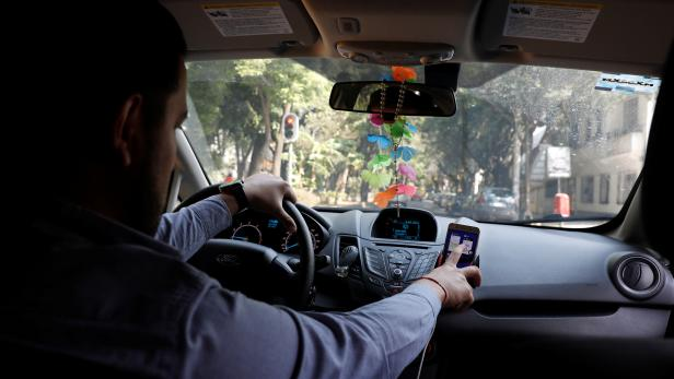 Uber driver checks the route on a mobile phone inside his car in Mexico City