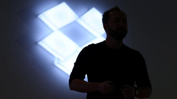 Drew Houston, Chief Executive Officer and founder of Dropbox, stands in front of the company's logo at an announcement event in San Francisco
