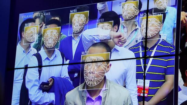 Visitors experience facial recognition technology at Face++ booth during the China Public Security Expo in Shenzhen