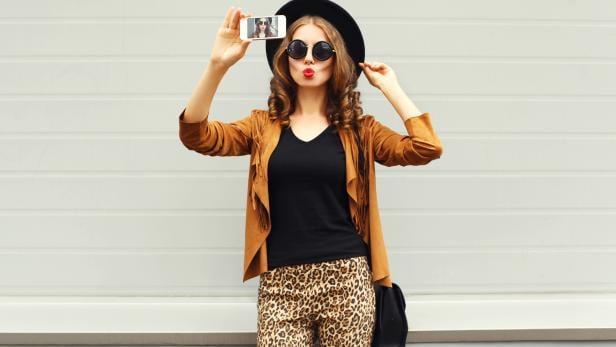 Fashion woman model taking photo picture self-portrait on smartphone
