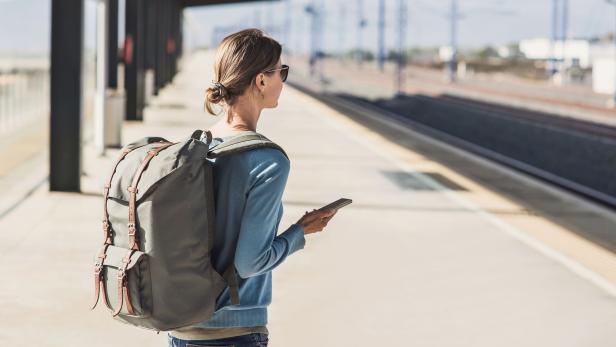 Young woman waiting for a train. Travel concept