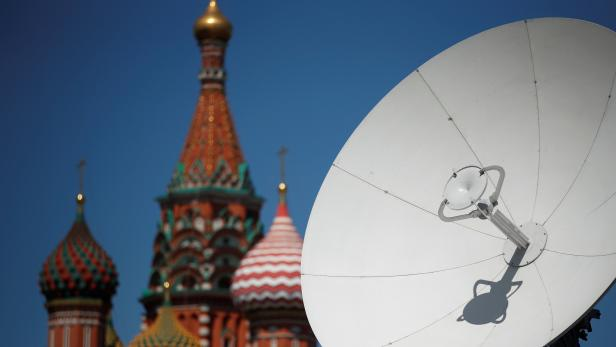 A TV satellite dish is seen in front of St. Basil's Cathedral in central Moscow