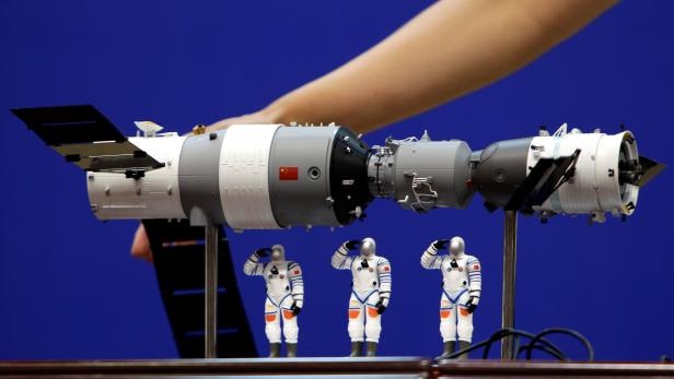 FILE PHOTO: A model of the Tiangong-1 space lab module, the Shenzhou-9 manned spacecraft and three Chinese astronauts is displayed during a news conference