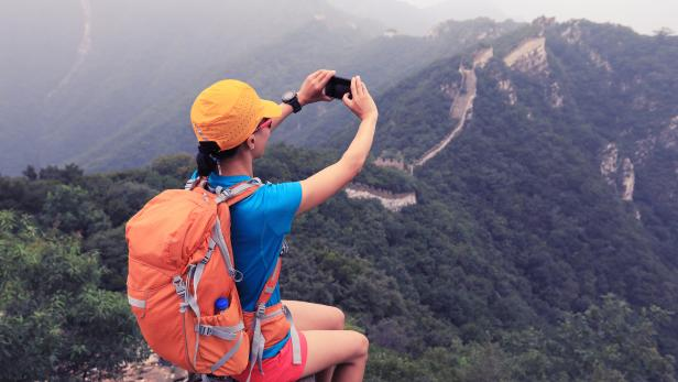young woman hiker taking photo with smart phone on top of great wall