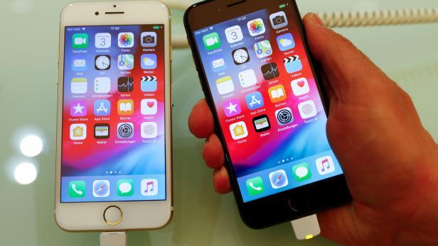An employee of German Apple retailer Gravis displays an iPhone 7 and 8 in a store in Berlin