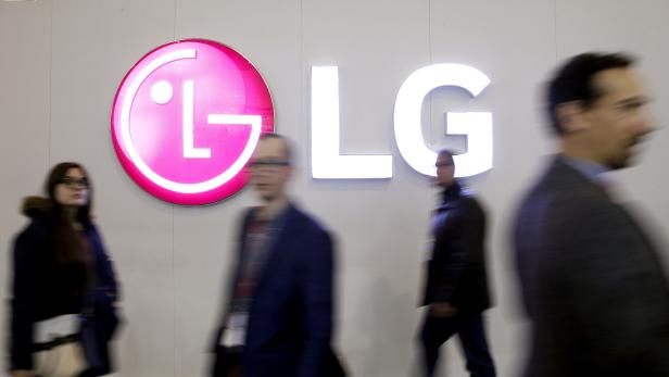 FILE PHOTO: People walk past an LG Electronics logo during the Mobile World Congress in Barcelona