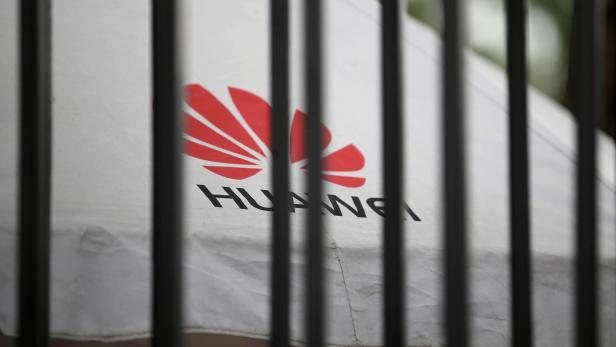 FILE PHOTO: A Huawei logo is seen outside the fence at its headquarters in Shenzhen