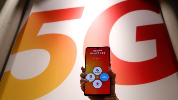 An employee displays a Huawei 5G Smartphone Mate 20X smartphone at a Sunrise telecommunications shop in Opfikon