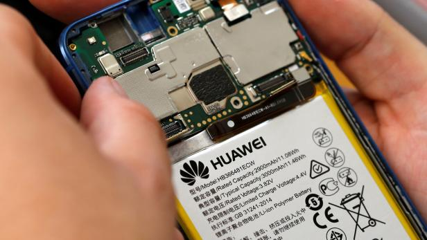FILE PHOTO: A worker refurbishes a Huawei cell phone at a workshop of the Oxflo company, specialised in refurbishment of broken European smartphones in Lusignac