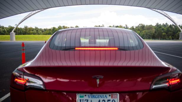 FILE PHOTO: IIHS media relations associate Young demonstrates a front crash prevention test on a Tesla Model 3 at IIHS-HLDI Vehicle Research Center in Ruckersville, Virginia