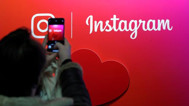 FILE PHOTO: A visitor takes a picture of the Instagram application logo at the Young Entrepreneurs fair in Paris