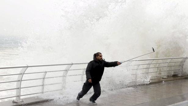 File photo of a man taking a selfie by a crashing wave on Beirut's Corniche, a seaside promenade, as high winds sweep through Lebanon during a storm