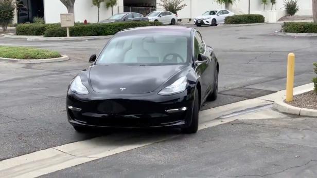 A Tesla 3 model is remotely driven with the company's phone app in Pomona, California