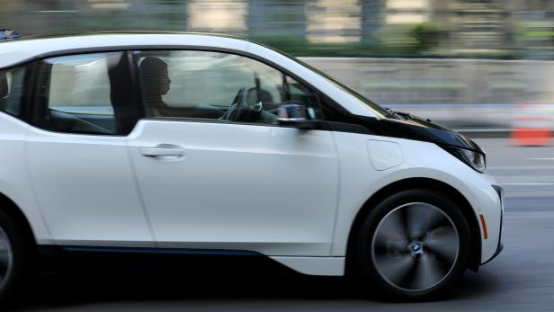 FILE PHOTO: A women drives an electric BMW i3 vehicle along a downtown street in Los Angeles,