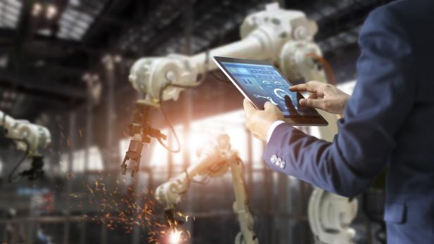 Manager industrial engineer using tablet check and control automation robot arms machine in intelligent factory industrial on real time monitoring system software. Welding robotics and digital manufacturing operation. Industry 4.0 concept