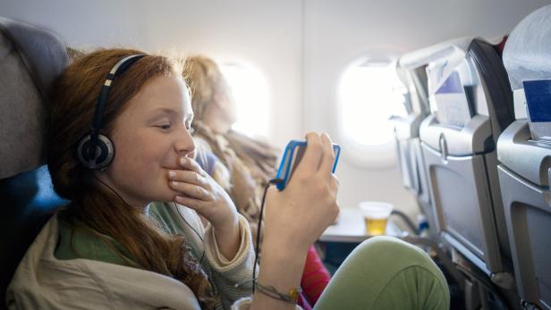 Girl on an airplane watching a movie on a mobile phone
