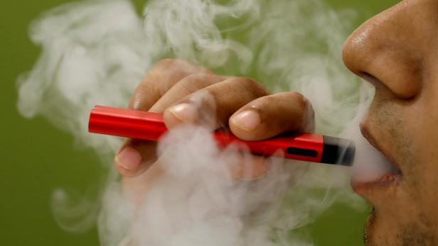 FILE PHOTO: A man uses a vape device in this illustration picture