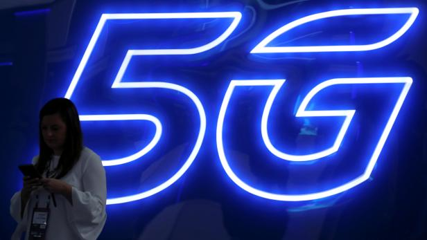 FILE PHOTO: A woman looks at her mobile phone next to a 5G sign at the Mobile World Congress in Barcelona