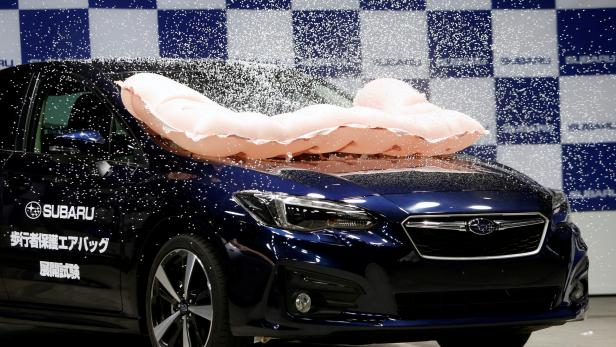 External airbag splashes mock snow, covering the surface of Subaru Impreza G4, as it is triggered during collision test demonstration, at its factory in Ota
