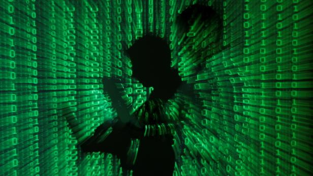 FILE PHOTO: An illustration picture shows projection of binary code on man holding aptop computer in Warsaw