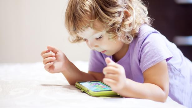 Cute little girl playing with smartphone.