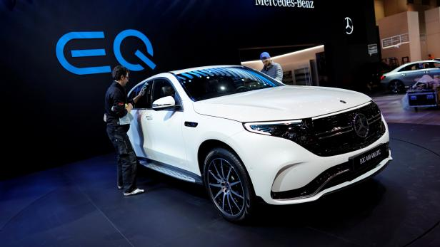 A man wipes down a Mercedes Benz EQC 400 4Matic electric vehicle at the Canadian International AutoShow in Toronto