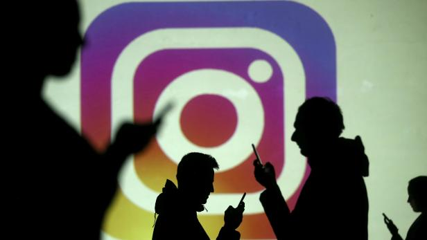 FILE PHOTO: Silhouettes of mobile users are seen next to a screen projection of Instagram logo in this picture illustration