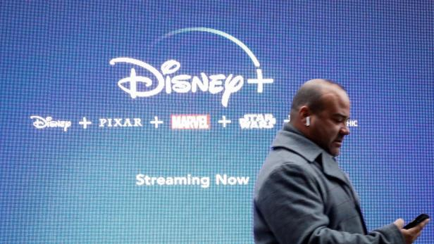FILE PHOTO: A man looks at his phone as he passes by a screen advertising Walt Disney's streaming service Disney+ in New York