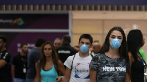 Passengers wearing masks, following the coronavirus outbreak in China, arrive at the Tom Jobim International Airport in Rio de Janeiro