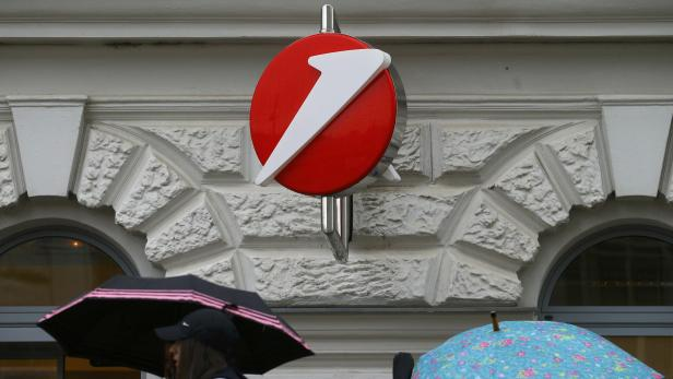 People carrying umbrellas pass a Bank Austria branch office in Vienna