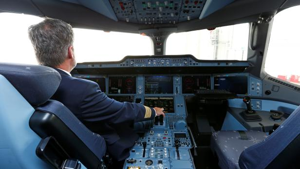 """A pilot poses in a cockpit of a Lufthansa Airbus A350-900 after the baptism of the 10th Lufthansa A350 to the name """"Erfurt"""", at Munich airport"""