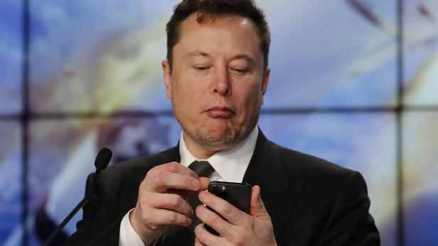SpaceX founder and chief engineer Elon Musk looks at his mobile phone during a post-launch news conference to discuss the  SpaceX Crew Dragon astronaut capsule in-flight abort test at the Kennedy Space Center