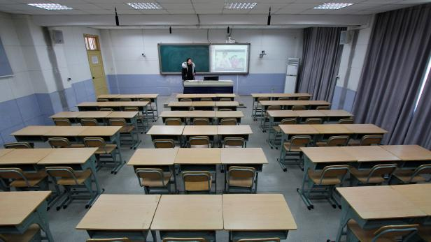 Teacher takes part in a recording of her lessons inside a classroom of a middle school, as students' return to school has been delayed due to the novel coronavirus outbreak, in Shaoyang