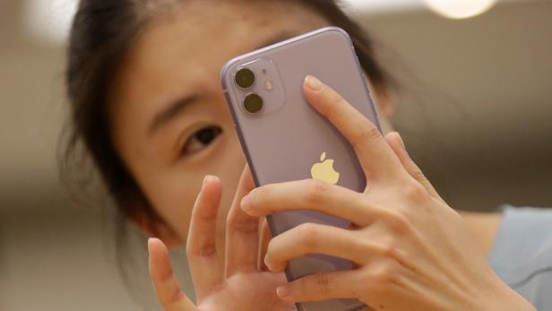 A customer tests Apple's new iPhone 11 after it went on sale at the Apple Store in Beijing