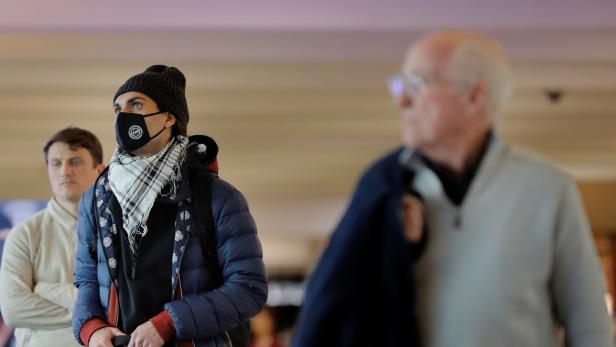 A traveler wears a mask in John F Kennedy International Airport in New York