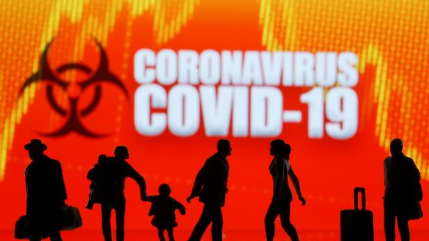 Small toy figures are seen in front of the coronavirus (COVID-19) sign in this illustration taken