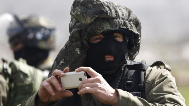 An Israeli soldier uses his mobile to take pictures during a protest against what Palestinians say is land confiscation for Jewish settlements, in Silwad