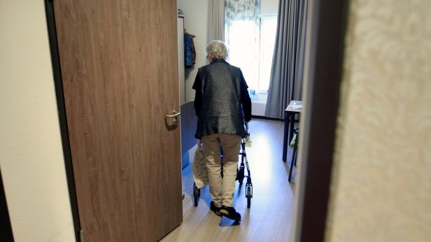 An elderly woman in a retirement home enters her apartment as visits have been restricted due to the coronavirus disease (COVID-19) concerns, in Grevenbroich