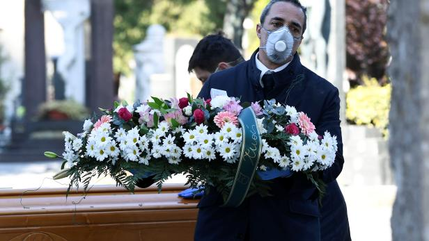 Cemetery workers and funeral agency workers in protective masks transport a coffin of a person who died from coronavirus disease (COVID-19), into a cemetery in Bergamo