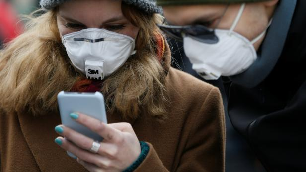 People wearing protective face masks use a smartphone on a street in Kiev
